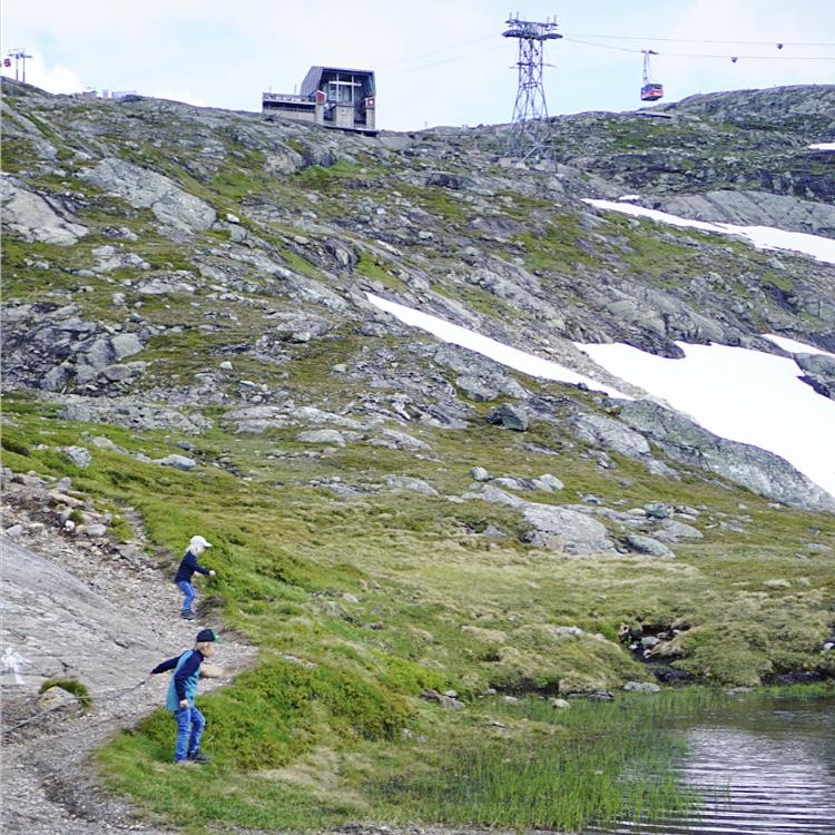 Love och Valter kastar stenar i sjö uppe på Åreskutan.